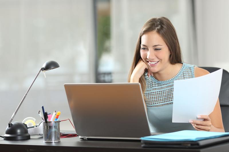 Frau sitzt lächelnd an Schreibtisch vor Laptop und hält Blatt Papier
