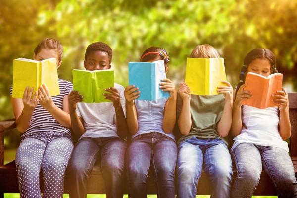 5 Kinder sitzen auf einer Bank und lesen Bücher