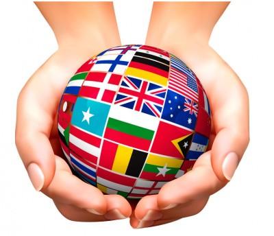 Zwei Hände halten eine Weltkugel mit Flaggen