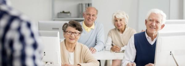 Ältere Menschen sitzen in Klassenzimmer und schauen Lehrer an